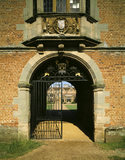 View through the archway of the gatehouse towards the east front with the gate half closed