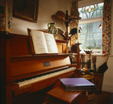 Room view of the Entrance Hall at Shaw's Corner, showing a Bechstein piano by the window with music volumes on the stool, hats, walking sticks, gaiter and open music book
