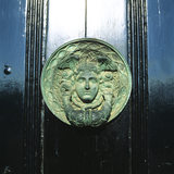 Detail of a bronze head on a plaque hanging on the door at the east end of the west wing at Ickworth