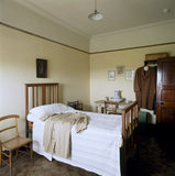 The Servant's Bedroom at Sunnycroft showing the wooden bedstead, chairs, wash stand and washing jug and basin
