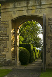 View through the stone entrance arch towards the topiary-flanked path leading from the road at Westwood Manor, near Bradford-on-Avon, Wiltshire