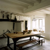 Room view of the Wet Kitchen at Woolsthorpe Manor showing table, benches, fireplace, window and cooking implements; the room has been restored to give an impression of a 17th century kitchen