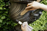 Cold waxing a bronze urn, using a brush to work wax into crevices and to remove excess wax from nooks and crannies