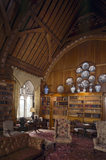 The Library at Tyntesfield, oak panelled throughout with arch- braced collar beam roof, inscribed upper frieze and oak fitted bookcases around the room