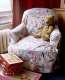 Lord Wraxall's Teddy Bear sitting on a chair with a nursery print cover, with a drum and a box of toys in front, at Tyntesfield