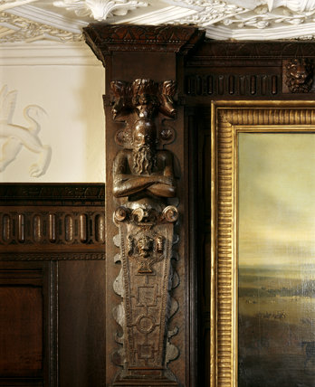 Detail of carved wooden figure above the fireplace in the Oak Room at Anglesey Abbey