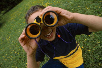 A young boy looks through a pair of bright yellow binoculars, straight at the photographers lens.MR