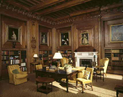 The panelled Library, with portraits and gold coloured upholstery on chairs