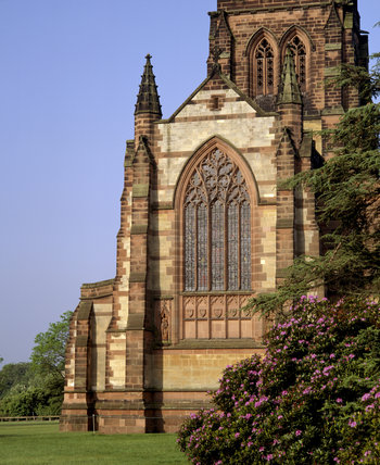 The east side of Clumber Chapel in soft sunlight seen from the from the shade of trees
