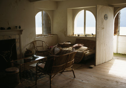 Interior of the boathouse at Greenway garden, with wicker furniture, fireplace and arched windows looking over the River Dart