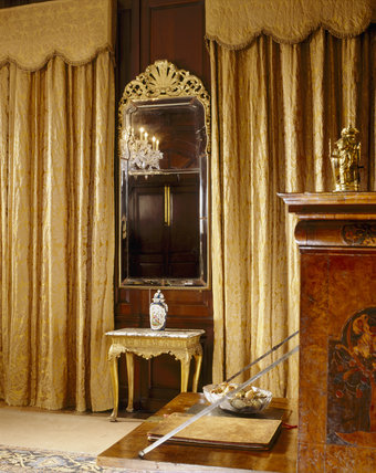 Partial room view of the Saloon at Antony House showing the Queen Anne pier-glass, made for the room with bevelled Vauxhall plate glass, and a gilt gesso Queen Anne side-table