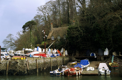 Close view of the approach to Greenway by the Red and Yellow Dittisham ferry, showing the runway to the ferry with boats on the left and a cottage and well-grown trees behind