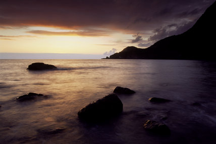 View of Woody Bay, North Devon with rocks in the foreground at sunrise