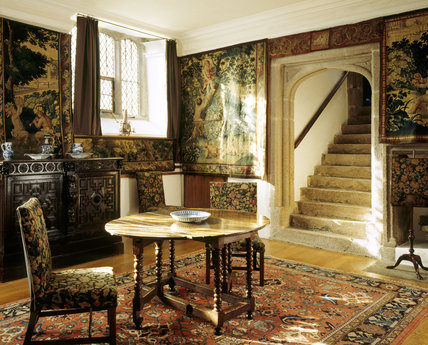 The Punch Room showing table, chairs, granite stairs and tapestries