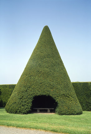 An unusual garden seat set in the middle of a topiary yew, trimmed into the form of a cone, in the garden of Antony