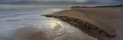 A striking image of the vast foreshore at Formby Point with sunlight falling on the sand as it breaks through the stormy sky
