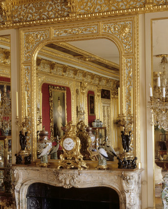 Partial view of the chimneypiece showing the mirror above the fireplace and mantelpiece with clock and candelabra of the Louis XV and Louis XVI periods