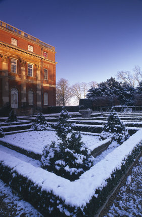 A view of Clandon House in the distance and the Parterre in the foreground covered in snow on a glorious winter's day and a warm sunlight glow on the house