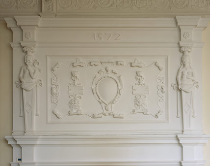 Detail of the scrolled plaster overmantel supported by finely modelled caryatids, dated 1572,  in the Hall at Trerice