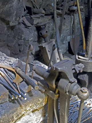 Close view of the vice clamped to the bench and various tools at Finch Foundry