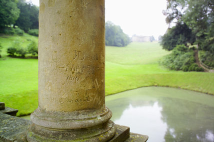 Initials engraved into the columns of the eighteenth-century Palladian Bridge at Prior Park, Bath, UK with the house (not NT) visible in the distance
