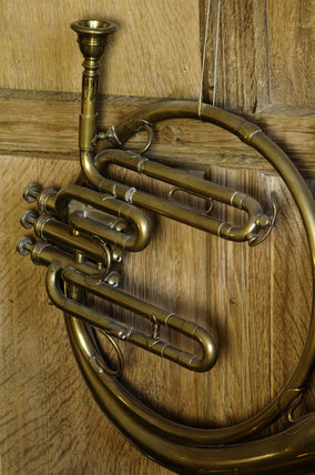 Close view of part of a tenor cor, part of the musical instrument collection in the Music Room at Snowshill Manor, Gloucestershire