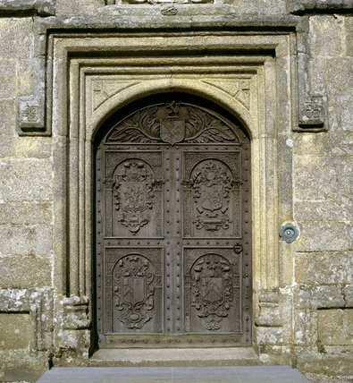 Close-up detail of the carved wooden door and stone surround in the Entrance Porch at Lanhydrock & Close-up detail of the carved wooden door and stone surround in the ...