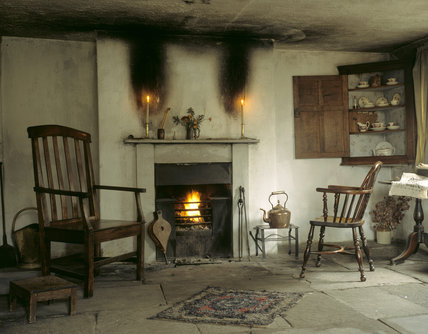 The Parlour of the Apprentice House on the estate at Styal, with lighted fire, fire-irons, bellows, copper kettle and wooden armchairs