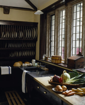 The scullery at Lanhydrock, view of the slate lined sink, draining board and wooden plate rack with fresh vegetables in foreground