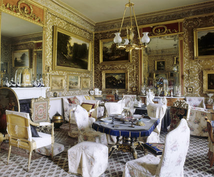 View of the Drawing Room at Calke Abbey showing the tables, giltwood armchairs, fireplace, giltwood firescreen, pier glasses and paintings either side