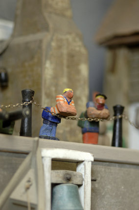 Close view of two wooden figures, part of the reconstruction of Wolf's Cove, the model village which was once in the garden at Snowshill Manor but is now in the room known as Occidens