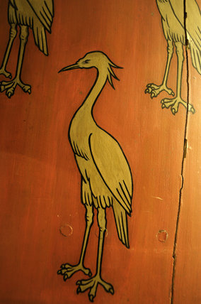 Close view of the painted detail on a wooden shield with three gold cranes in the Front Staircase and Green Room Corridor at Snowshill Manor