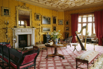 View of The Drawing Room at Charlecote Park including; a centre table, chimneypiece, candle stands, mirror, stools, chairs, paintings and a harp