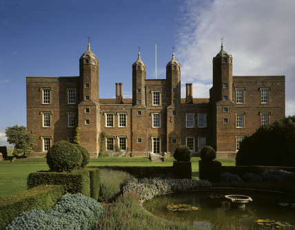 The West Front of Melford Hall, a red brick house built in the C16th, showing 4 towers & ogee roof