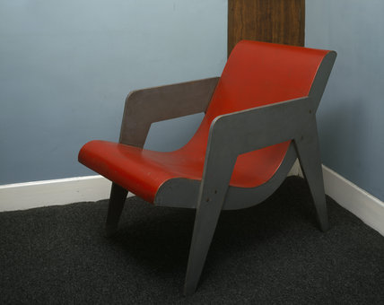 A wooden chair designed by Erno Goldfinger, painted red and grey