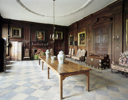 Room view of Entrance Hall with C17th refectory table, settees, fireplace and wooden chests
