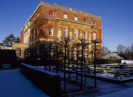 The south west corner of the house at Clandon, lit by a winter sun, seen through a group of bare hornbeams and across the snow - covered parterre