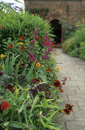 The double border and path to the pavilion in the garden at Packwood House, with Rudbeckia, Sedum, Penstemon, Tradescantia and Crocosmia