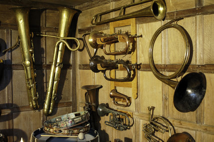 Part of the musical instrument collection of Charles Paget Wade, including ophicleide, slide trumpet, coach horn and bugle,  in the Music Room at Snowshill Manor, Gloucestershire