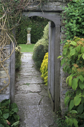 A view through an arched gateway from the Apostle Garden to the Main Border area at Lytes Cary Manor