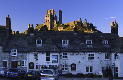 The thousand-year-old Corfe Castle at Wareham, Dorset, UK, bathed in a warm light above the public house and village below