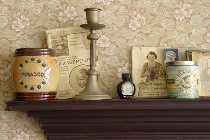 A candlestick, tobacco jars and printed ephemera on the mantlepiece of the front parlour of the 1930s house in the Birmingham Back to Backs