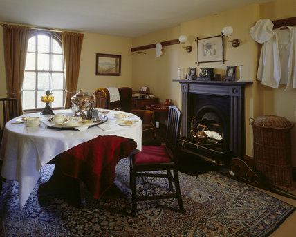 The Cook's Sitting Room, table laid for tea with hot muffins and a copper kettle, cook's uniform hanging on a peg