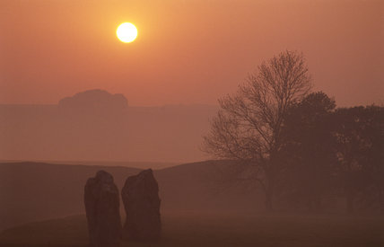 Sunrise at Avebury with the stones rising out of the morning mist and a deep orange sky behind