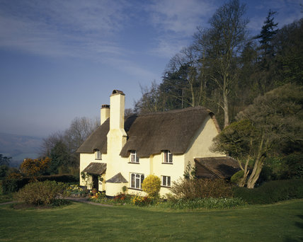 A creamed washed cottage at Selworthy, Somerset, with a thatched roof and diamond paned leaded windows