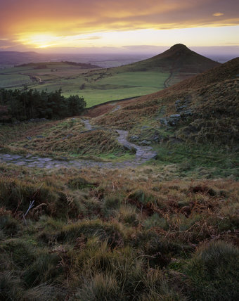A panoramic view of Roseberry Topping under a dramatic sky, created by the setting sun