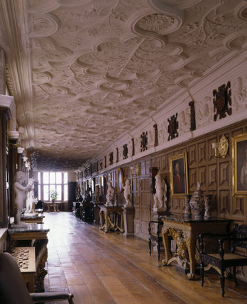 View of the Long Gallery at Powis Castle showing the ceiling, furniture and window at the far end