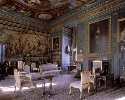 View of the Blue Drawing Room at Powis Castle, showing the fireplace, pair of commodes with ormolu mounts attributed to Pierre Langlois, ceiling, wall tapestry and sofa suite