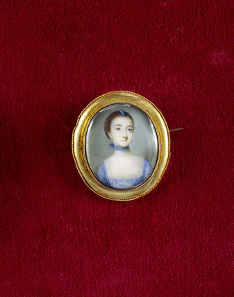 A minature portrait of a women in a blue dress trimmed with lace