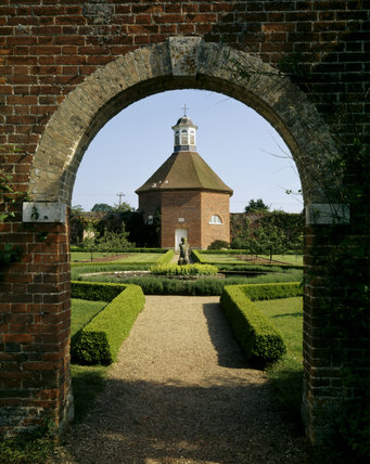 Manicured lawns and hedgerows lead up to the octagonal Dovecote in the Walled Garden at Felbrigg